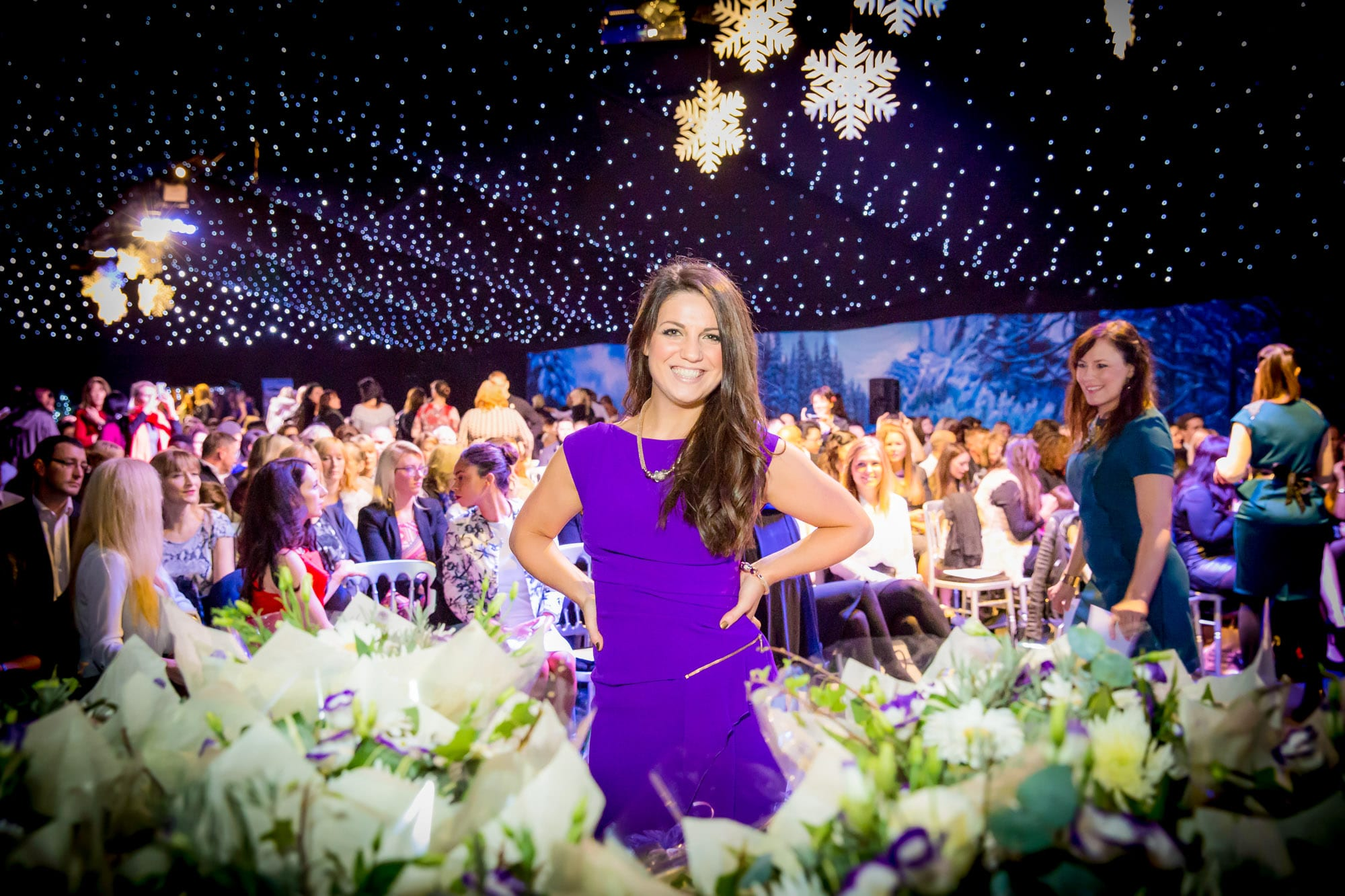 Woman surrounded by flowers at event