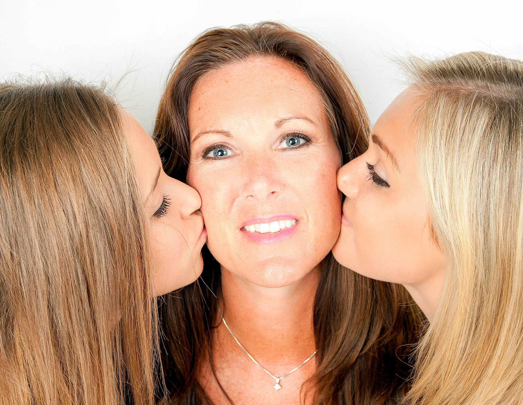 Daughters kissing mum on the cheeks