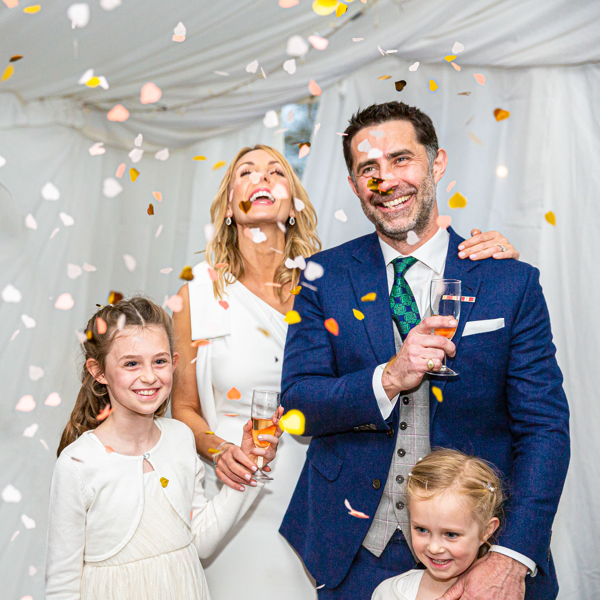 Bride, Groom and children showered with confetti.
