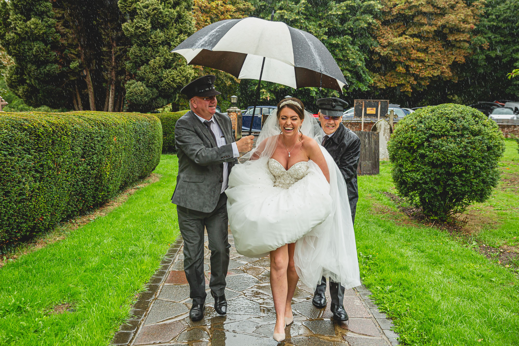 Bride running to the church through the rain